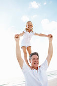 Portrait of a playful daughter standing on father's shoulder on beach