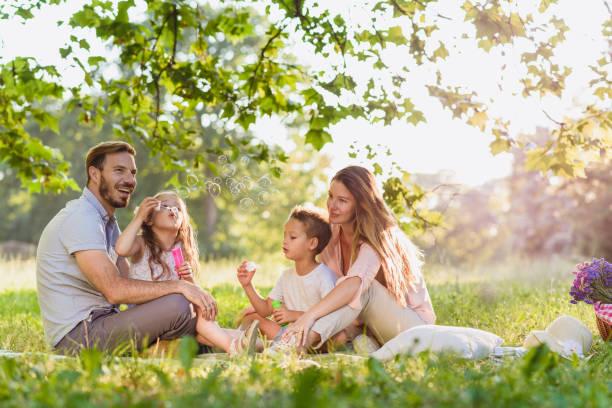playful family blowing bubbles and laughing togther - mãe criança brincar relva efeito de refração de luz imagens e fotografias de stock