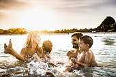 Young happy family having fun while splashing water in sea at sunset. Copy space.