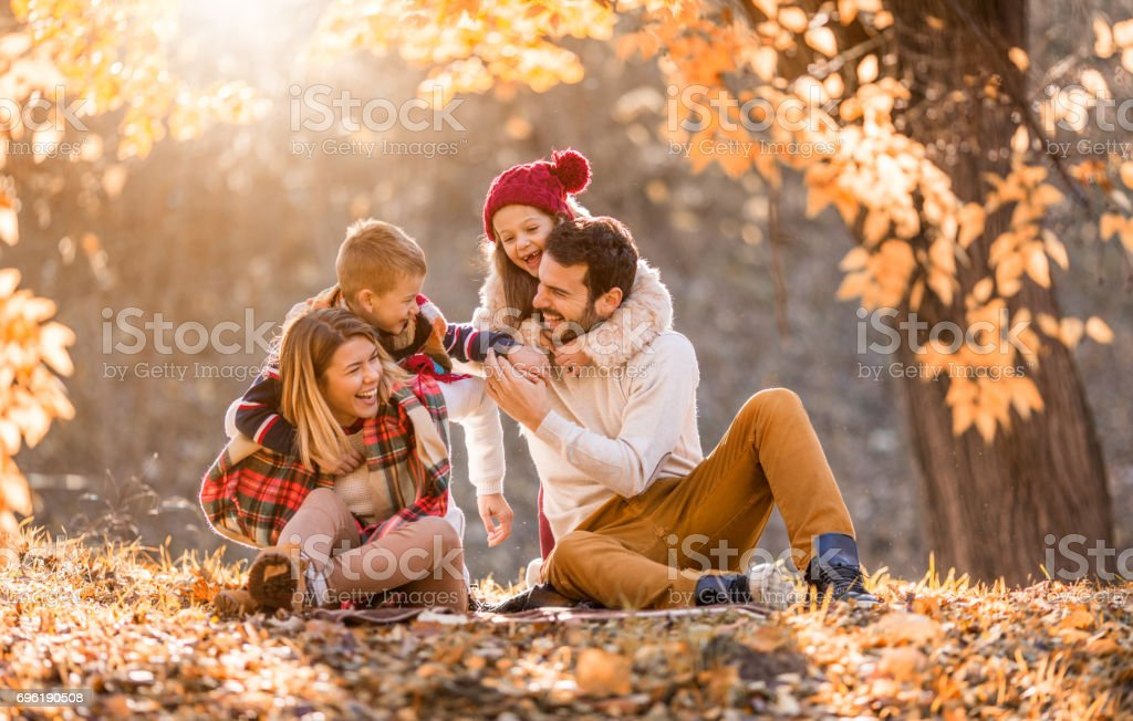 Playful family having fun in autumn day at the park. stock photo