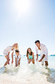 Happy family having fun in summer day. They are standing in the sea and splashing water. Copy space.