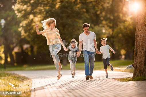 istock Playful family having fun while holding hands in the park. 1127488144
