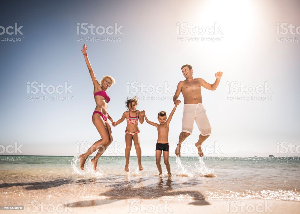 Playful family having fun while jumping on the beach. stock photo
