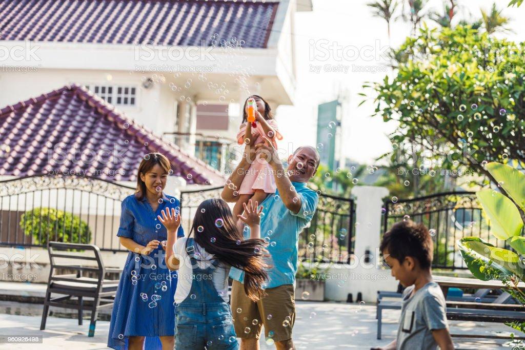 Eine spielerische Familie auf dem Hinterhof in Malaysia – Foto