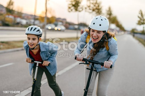 Photo of boy with his mother riding a scooter