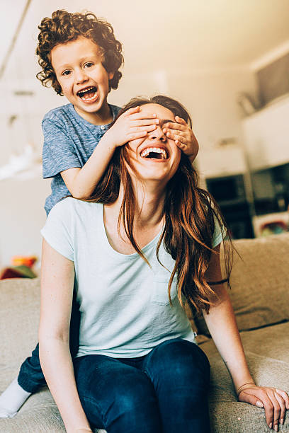 Playful family Mother and son playing in a living room. hide and seek stock pictures, royalty-free photos & images