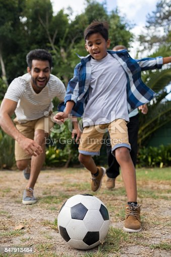 829627936istockphoto Playful family playing soccer on field 847913464