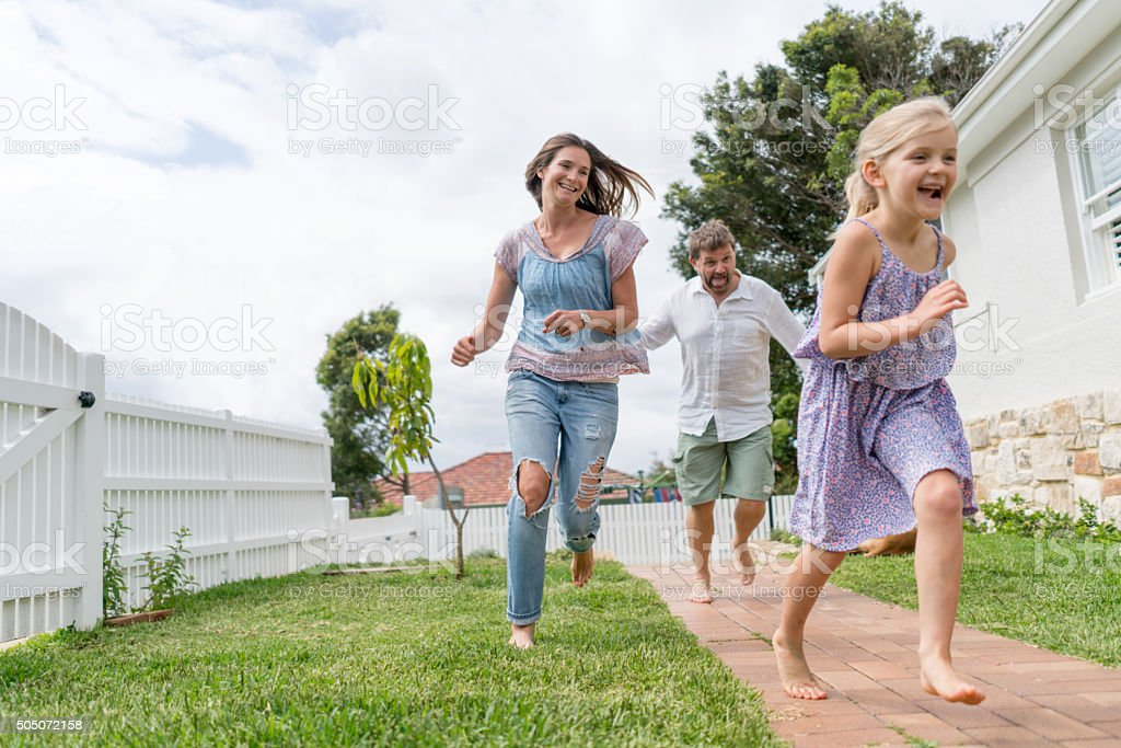 Playful family running around the house stock photo