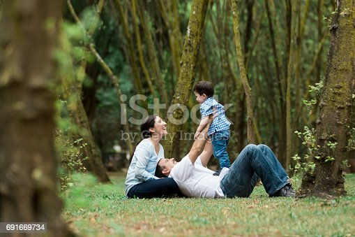 811227514 istock photo Playful family with one child sitting on the grass 691669734