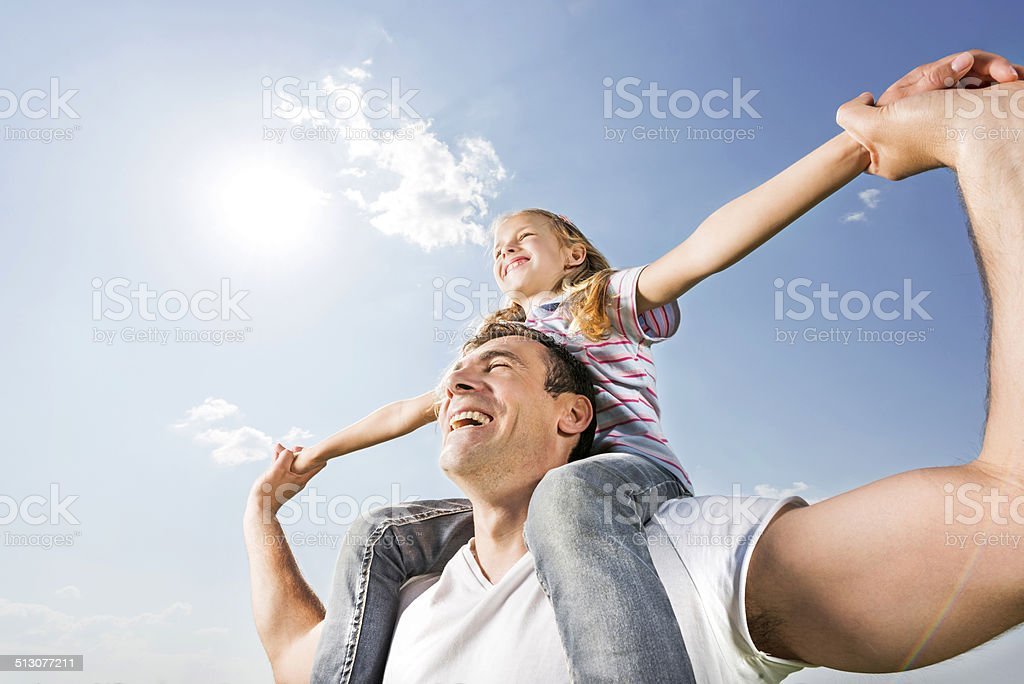 Playful father and daughter against the sky. stock photo