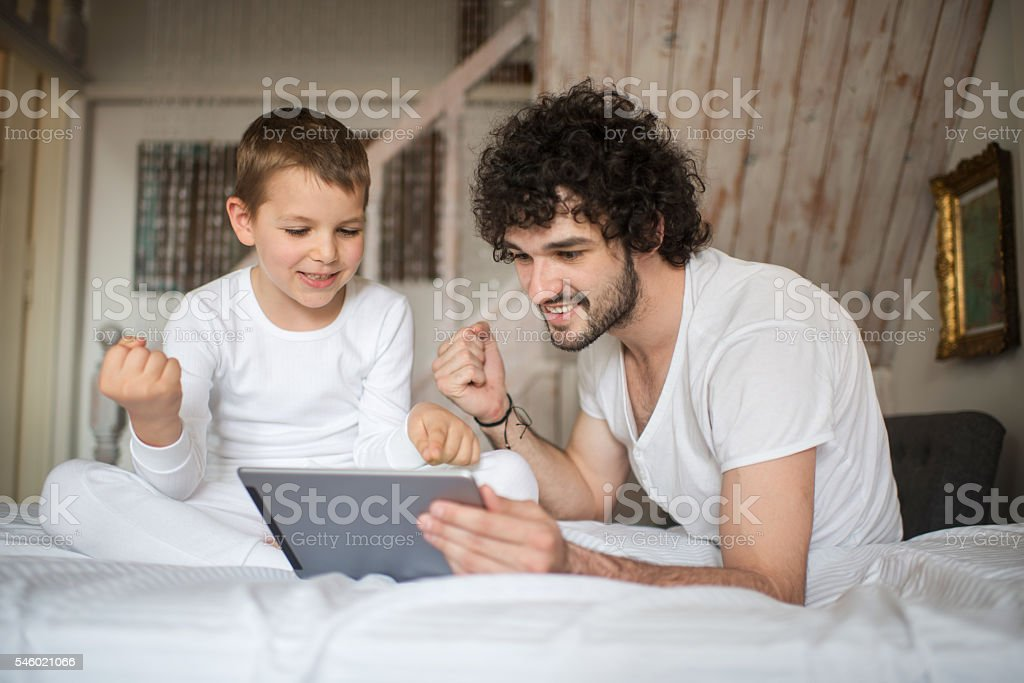 Playful father and son celebrating while using touchpad in bedroom. stock photo