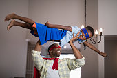 Playful father and son in superhero costume playing at home