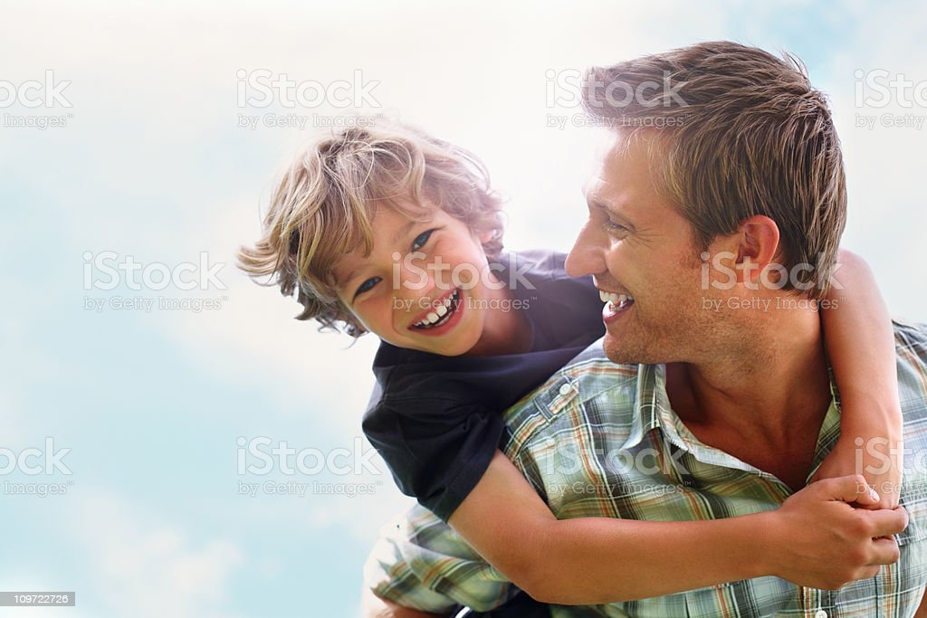 Playful father giving his son piggy back ride against sky stock photo