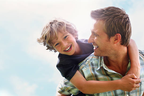 Playful father giving his son piggy back ride against sky  piggyback stock pictures, royalty-free photos & images