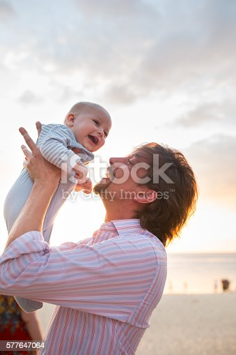 istock Playful father with baby on the beach at sunset. 577647064