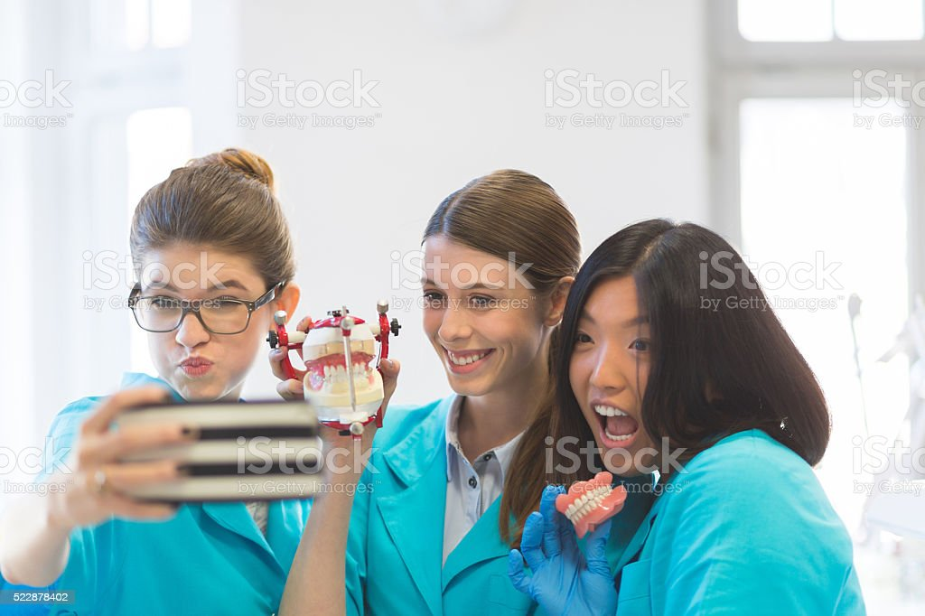 Playful female students learning prosthetic dentistry, taking selfie stock photo