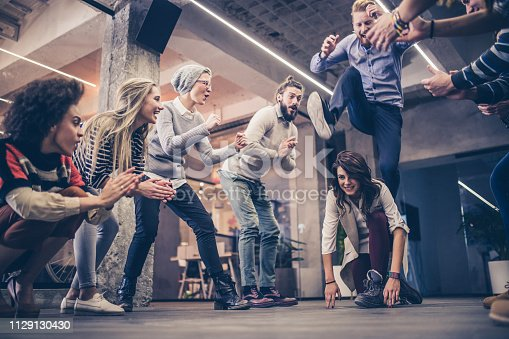 Large group of happy entrepreneurs having fun while applauding their colleagues during leapfrog game in the office.