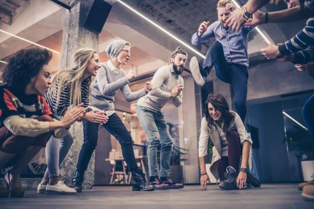 freelancers lúdicas se divertindo em uma pausa no escritório casual. - escapismo - fotografias e filmes do acervo
