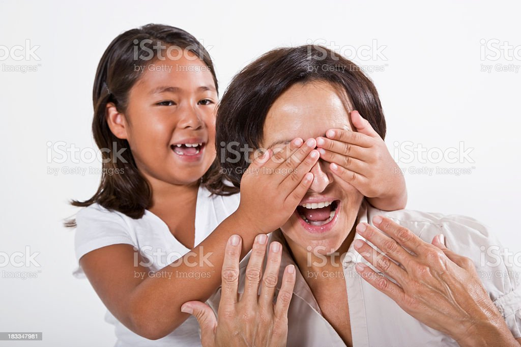 Playful girl covering grandmother's eyes royalty-free stock photo
