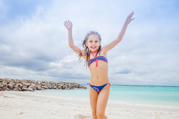 playful girl enjoying the beach holiday - girl alone in swimsuit stock photos and pictures