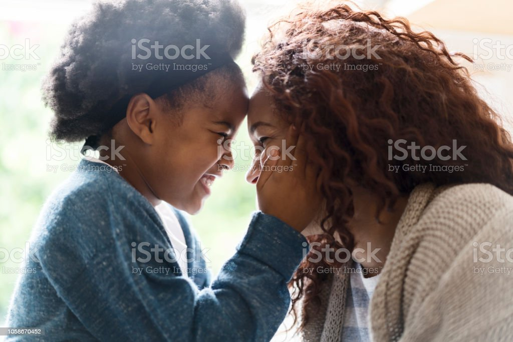 Side view of cheerful mother and daughter enjoying at home. Playful...