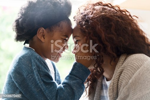 Side view of cheerful mother and daughter enjoying at home. Playful girl is face to face with woman. They are spending leisure time.
