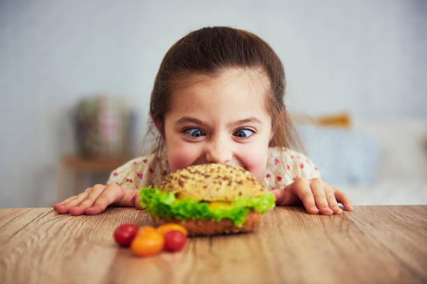 Playful girl looking at delicious hamburger stock photo