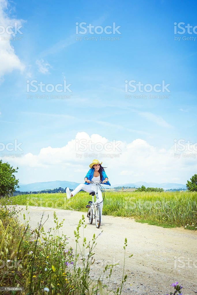 Playful girl on a bicycle by green fields royalty-free stock photo