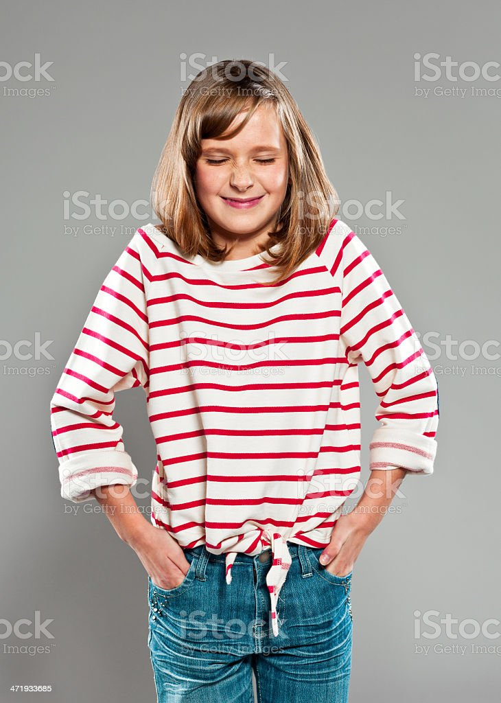 Playful girl Portrait of cute girl wearing striped blouse smiling with hands in pockets. Studio shot, grey background. 10-11 Years Stock Photo