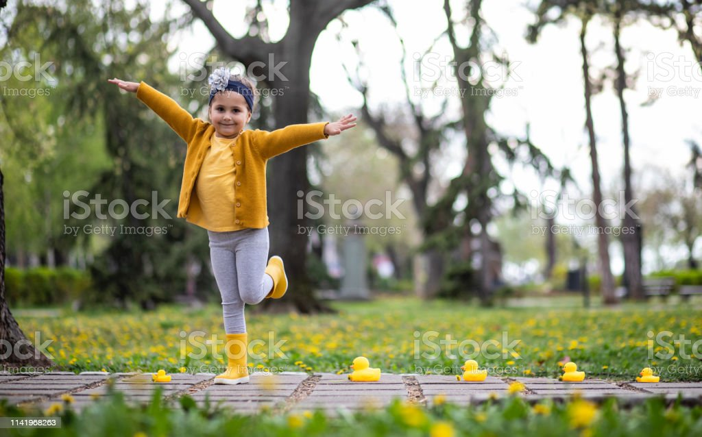 Cute playful girl playing around the park with her toys.