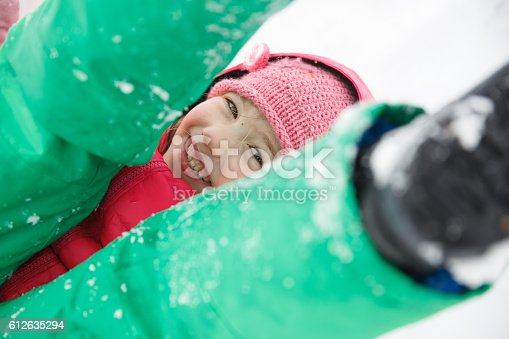 istock Playful girl with braids playing in the first snow 612635294