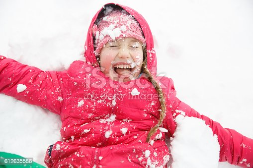 istock Playful girl with braids playing in the first snow 612635586