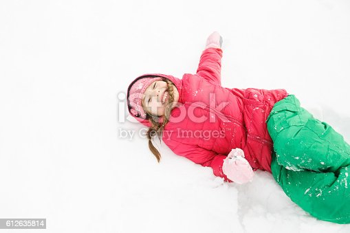 istock Playful girl with braids playing in the first snow 612635814