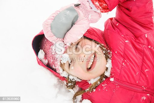 istock Playful girl with braids playing in the first snow 612635960