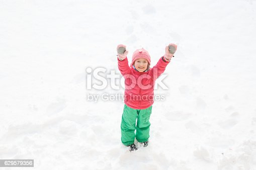 istock Playful girl with braids playing in the first snow 629579356