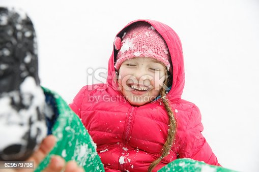 istock Playful girl with braids playing in the first snow 629579798
