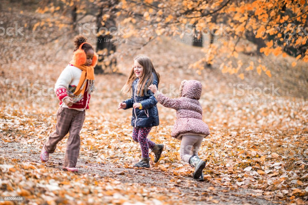 Playful girls chasing each other in the forest. stock photo