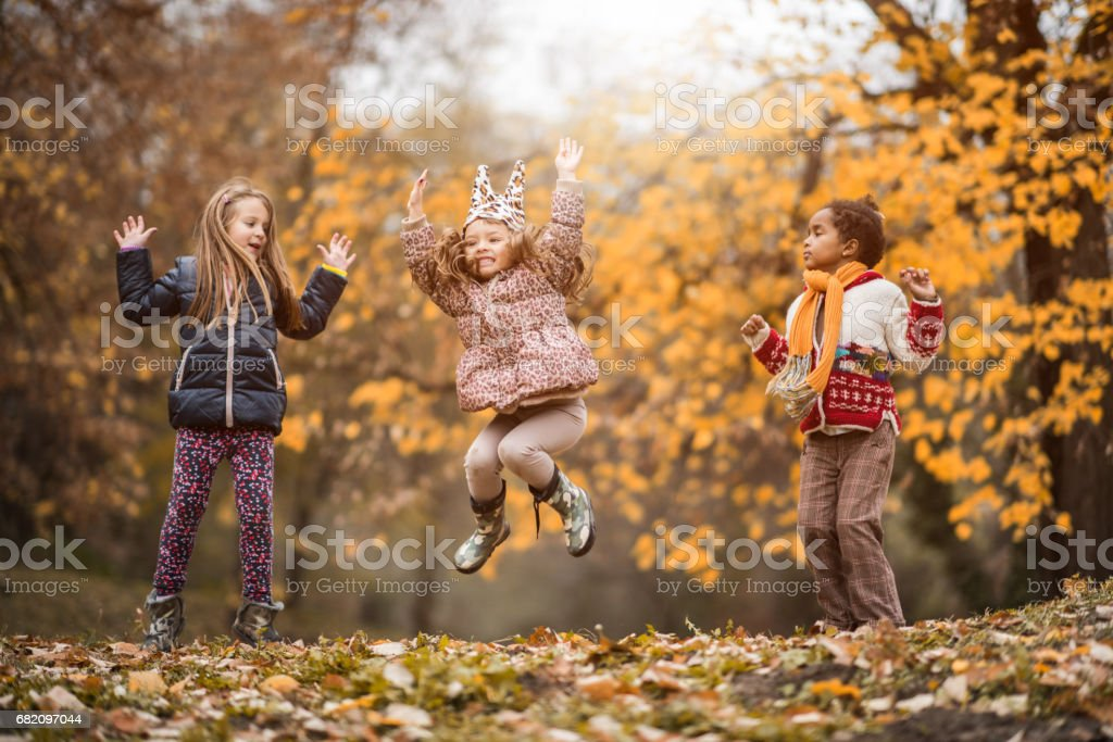Playful girls having fun while jumping in the park. stock photo