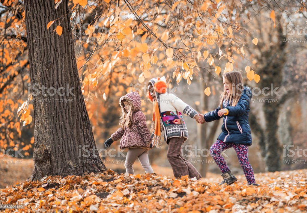 Playful girls having fun while running in the forest. stock photo