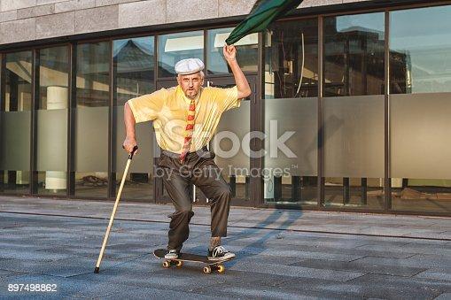 istock Playful grandfather on a skateboard. 897498862