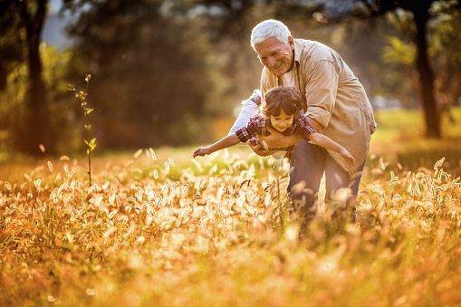 Close up of a playful grandfather playing with his grandson outdoors
