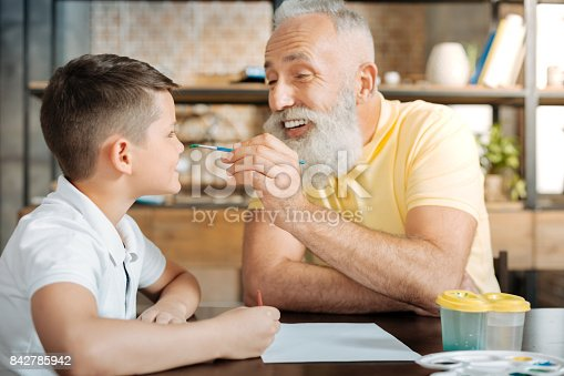 istock Playful grandfather putting a watercolor dot on grandsons nose 842785942