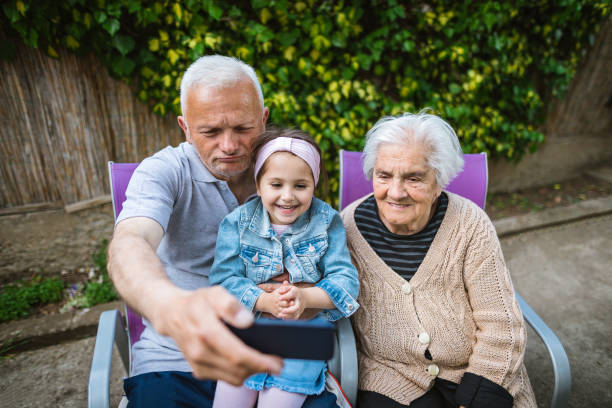Playful grandparents amuse granddaughter Cheerful 4 year old child enjoy spending time with her grandparents in backyard of their house. amuse stock pictures, royalty-free photos & images