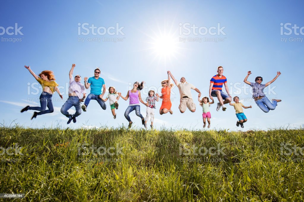 Playful group of happy people jumping against the sky. stock photo