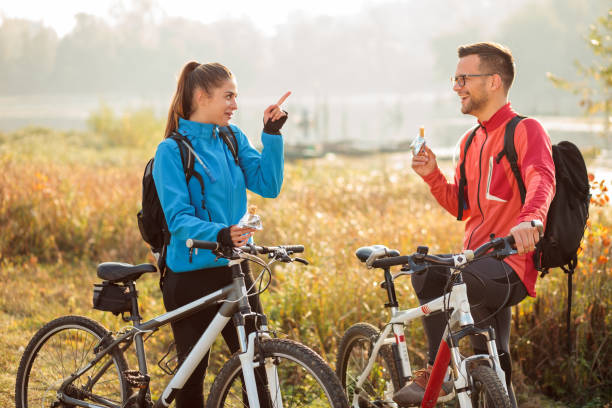 Playful happy young couple eating energy bars while taking a break from an early morning bicycle ride by the lake or river. Playful happy young couple eating energy bars while taking a break from an early morning bicycle ride by the lake or river. Active and healthy lifestyle female biker resting stock pictures, royalty-free photos & images