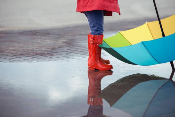 playful kid on rainy day. - kinder winterstiefel stock-fotos und bilder
