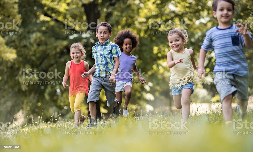 Playful kids feeling free while running in the park. Group of happy children having fun while running in nature. Focus is on African American boy looking at the camera. African Ethnicity Stock Photo