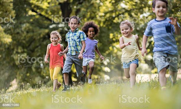 Playful Kids Feeling Free While Running In The Park Stock Photo - Download Image Now