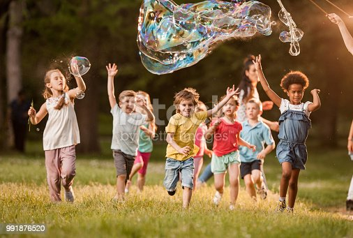 Large group of carefree children having fun while running in the park. Above their are rainbow bubbles.