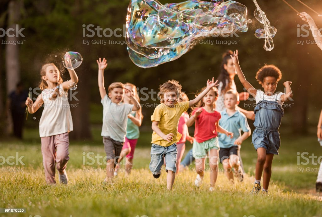 Playful kids having fun while running below rainbow bubbles in nature. stock photo
